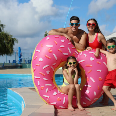 Happy family with inflatable ring near swimming pool.  Summer vacation